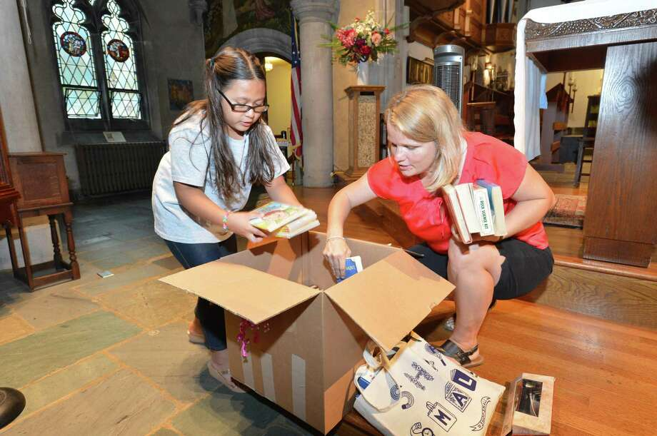 9 yr old Hayley Chavarria unpacks a box of gifts and books collected with help from Terra Volpe and  Action Together CT on Tuesday August 15, 2017 in Norwalk Conn. The group collected hand written letters from children all over Connecticut to present to Hayley and her mother Nury Chavarria at St. Pauls on the Green church Photo: Alex Von Kleydorff / Hearst Connecticut Media / Norwalk Hour