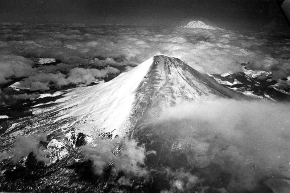 Aerial view  Mount St. Helens after the volcano erupted,  March 31, 1980 a more massive and devastating eruption would happen May 18,  1980 Mount Ranier is seen in the background. Photo ran 07/13/1988, P. B4