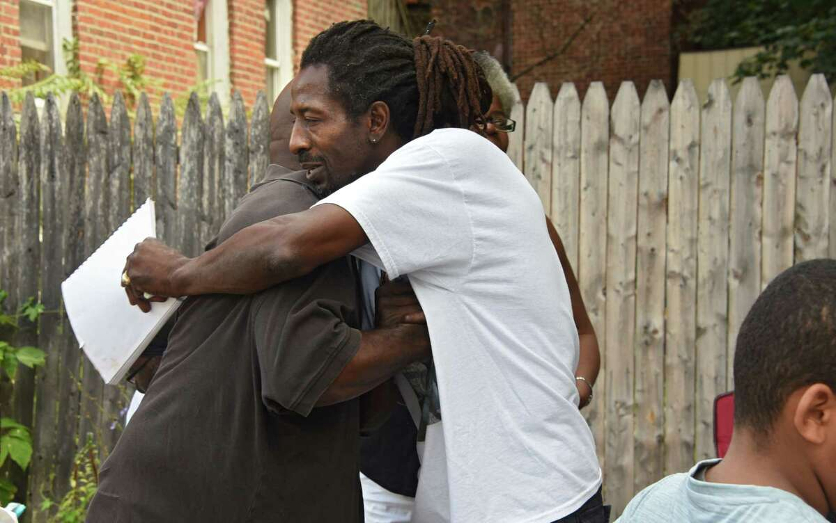 Donald Jackson, left, hugs Messiah Cooper, both of Troy, before a rally to protest the shooting of Dahmeek McDonald on Wednesday, Aug. 16, 2017 in Troy, N.Y. A police officer shot the 22-year-old during a traffic stop. (Lori Van Buren / Times Union)