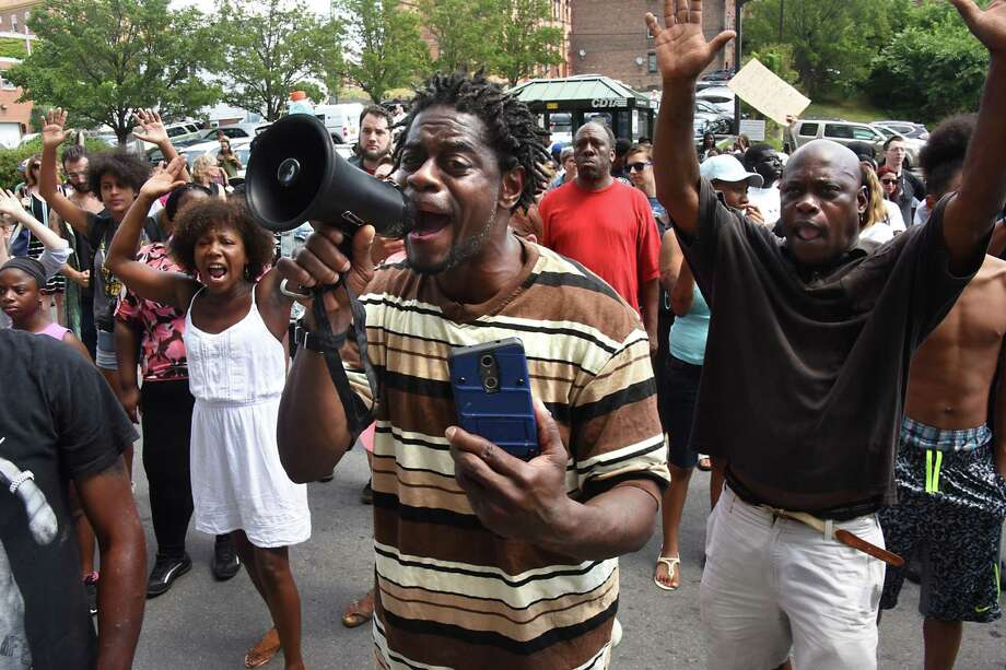 "William Felder of Troy leads a chant of ""hands up, don't shoot"" while holding a megaphone outside Troy City Hall during a protest of the shooting of Dahmeek McDonald on Wednesday, Aug. 16, 2017 in Troy, N.Y. A police officer shot the 22-year-old during a traffic stop. (Lori Van Buren / Times Union) Photo: Lori Van Buren, Albany Times Union / 20041306A"