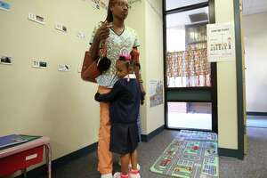 Leah Jackson, 4, holds on to her mother's, Tameishia Campbell, legs during her first day of pre-kindergarten at Best Elementary School Wednesday, Aug. 16, 2017, in Houston.