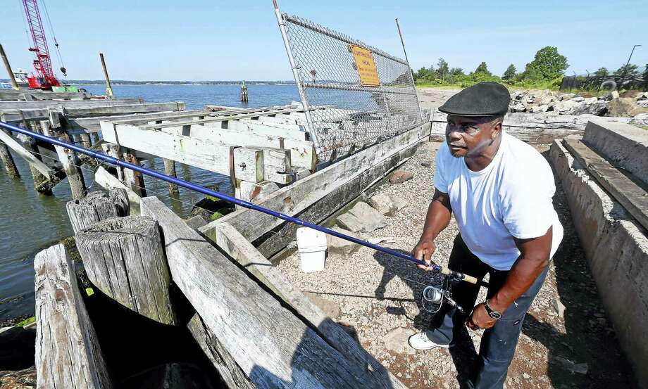 Andre Craig of Hamden fishes by a storm-damaged pier at Fort Hale Park in New Haven Wednesday. Photo: Arnold Gold / Hearst Connecticut Media / New Haven Register