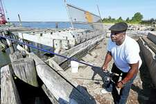Andre Craig of Hamden fishes by a storm-damaged pier at Fort Hale Park in New Haven Wednesday.