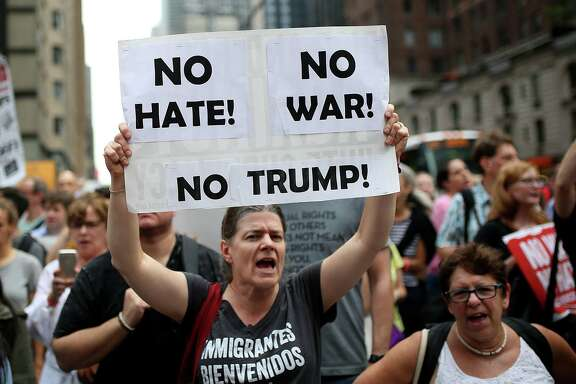 "NEW YORK, USA - AUGUST 14 : A protester holds a banner reading ""No Hate - No War - No Trump"" during a rally against U.S. President Donald J. Trump for threating North Korea and Venezuela with attacking next to Trump Tower in Manhattan borough of New York, United States on August 14, 2017. (Photo by Mohammed Elshamy/Anadolu Agency/Getty Images)"