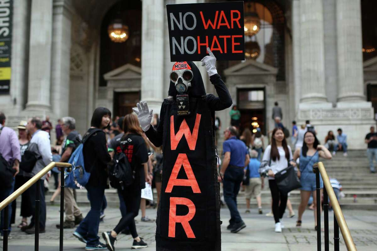 """A protester with a costume holds a banner reading """"No War No Hate"""" during a rally against U.S. President Donald J. Trump for threating North Korea and Venezuela with attacking next to Trump Tower in Manhattan borough of New York, United States on August 14, 2017."""