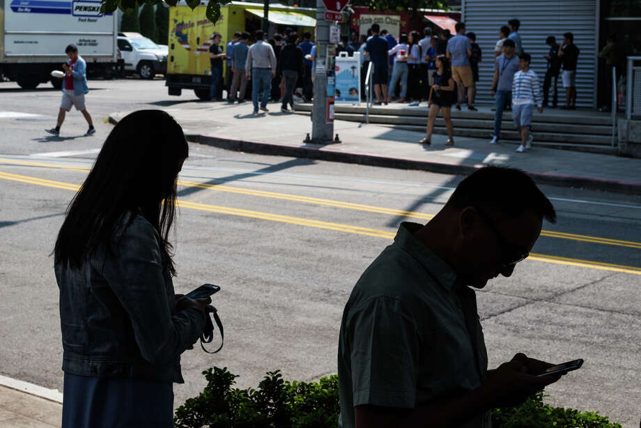 Food truck patrons wait in line while on checking their smartphones on Aug. 10, 2017. Photo: GRANT HINDSLEY, SEATTLEPI.COM / SEATTLEPI.COM