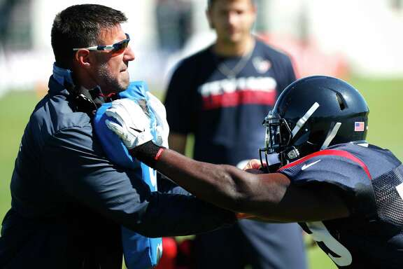 Texans defensive coordinator Mike Vrabel, left, works with outside linebacker Whitney Mercilus during training camp.