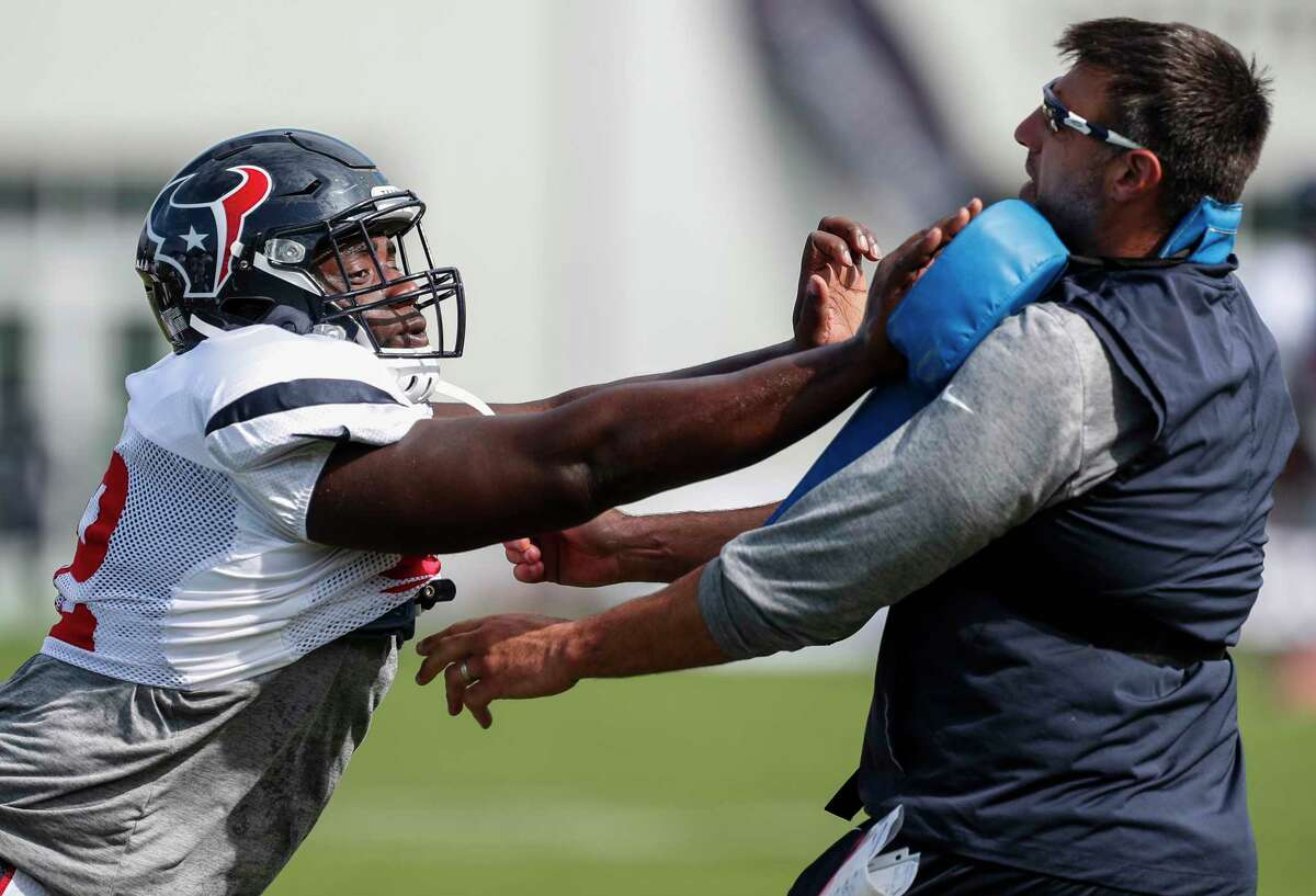 Houston Texans defensive tackle Brandon Dunn, left, hits a blocking pad held by defensive coordinator Mike Vrabel during training camp at The Greenbrier on Saturday, Aug. 12, 2017, in White Sulphur Springs, W.Va. ( Brett Coomer / Houston Chronicle )
