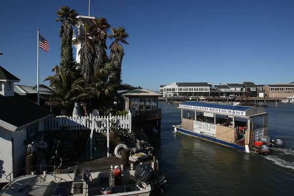An overview of the floating restaurant, Forbes island, taken from Pier 41 looking towards Pier 39 in San Francisco, Calif., on Thursday, July 1, 2010.  The motorboat (right) is driven by owner Mr.Forbes who picks up visitors from the dock and offers a mini tour.
