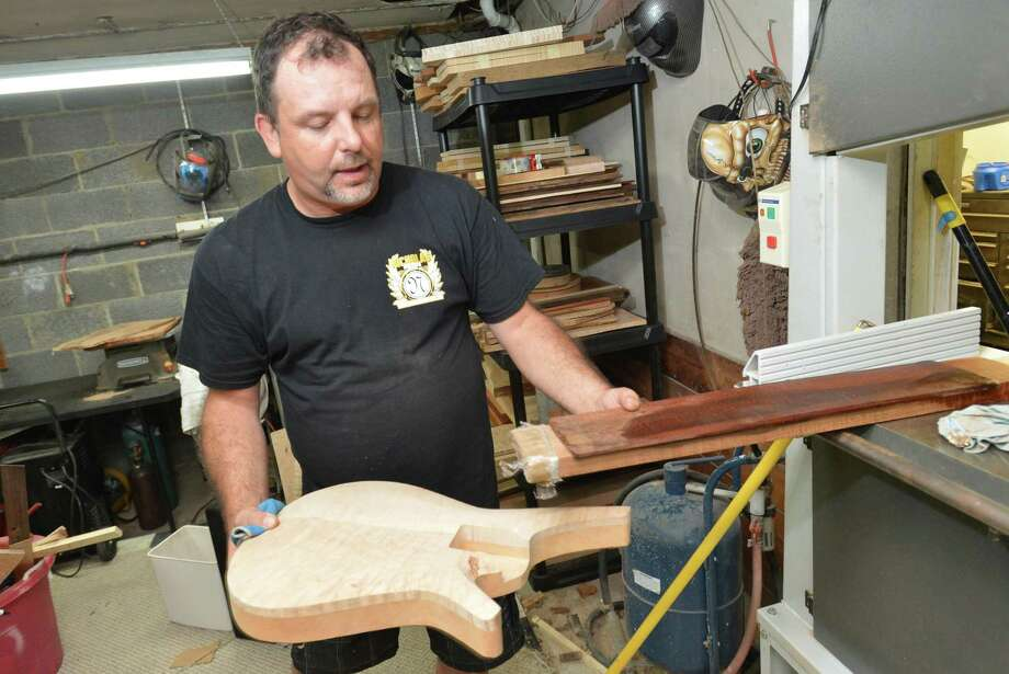 Nick Townsend looks over choices from his supply of wood for the neck of a guitar body he is making in his Norwalk studio on Wednesday August 16, 2017. Nick designs and builds custom hand made guitars for his business Nicholas Guitars. Photo: Alex Von Kleydorff / Hearst Connecticut Media / Norwalk Hour