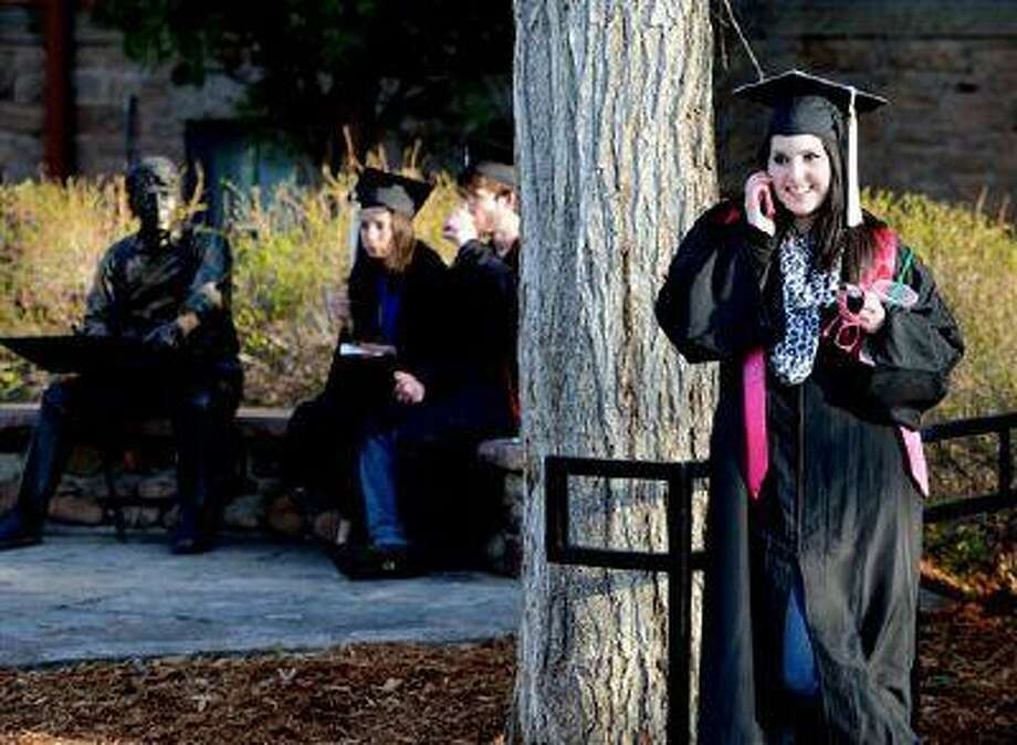 Lauren Shirley, right, makes a call while Carina Kee and Witt Keller have breakfast near the Robert Frost statue before the 2013 University of Colorado Spring in Boulder, Colo. (AP Photo/The Daily Camera/Cliff Grassmick) Photo: AP / The Daily Camera