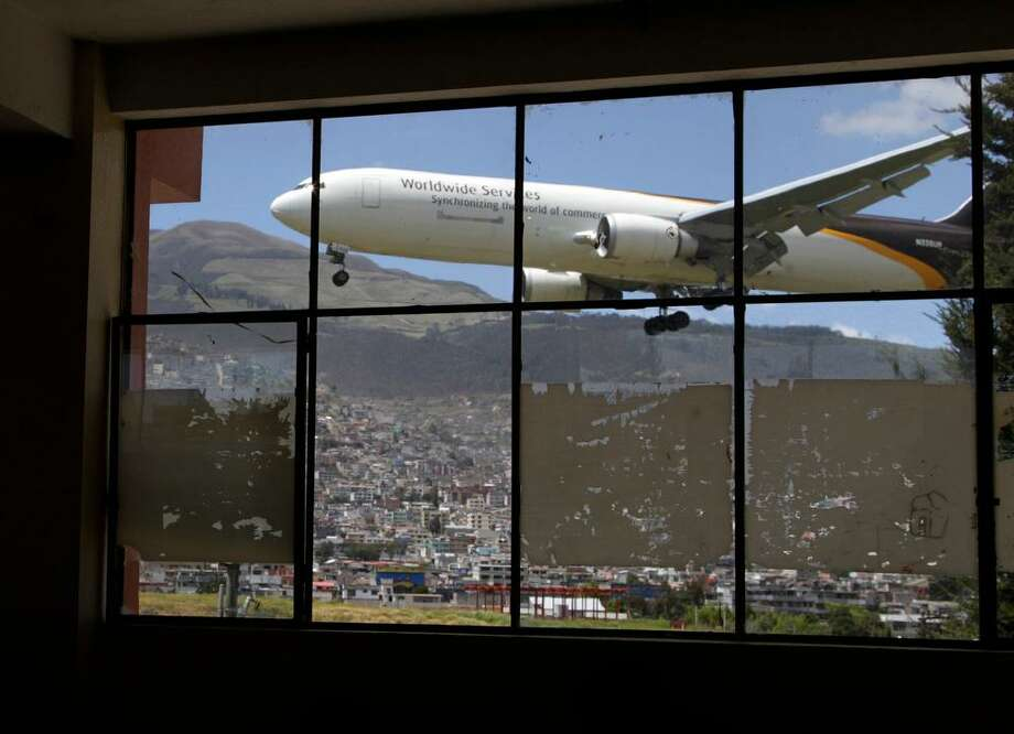 In this Jan. 8, 2013 photo, a plane approaches the Mariscal Sucre airport for landing, seen through a glass wall inside the Eloy Alfaro school in Quito, Ecuador.  Landing at Ecuadorís capital can be a white-knuckle affair. High altitude, a cramped runway and towering, active volcanos nearby make it one of Latin Americaís most challenging aiports for pilots. And the constant roar of the planes has tormented those on the ground as well. Mariscal Sucre airport sat amid cornfields when it was christened in 1960, and on Feb. 19, the airport will close and a new airport will be built in an agricultural setting 12 miles (20 kilometers) northeast of the capital. (AP Photo/Dolores Ochoa) Photo: ASSOCIATED PRESS / AP2013
