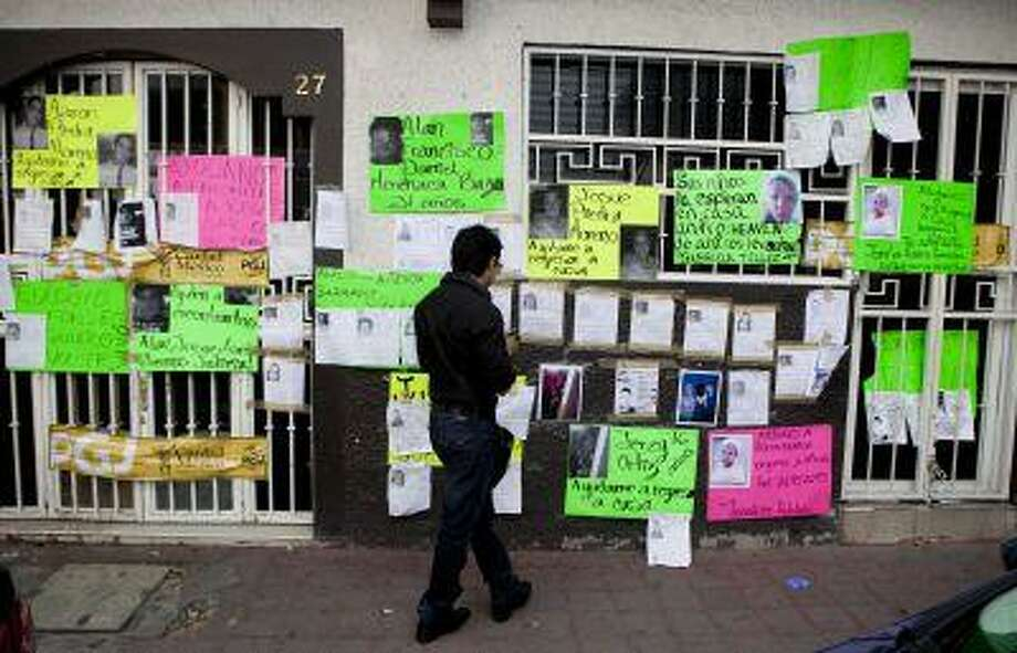 A man looks at pictures and posters of recently disappeared people, on the facade of a bar entrance in Mexico City, Thursday, May 30, 2013. Photo: ASSOCIATED PRESS / AP2013