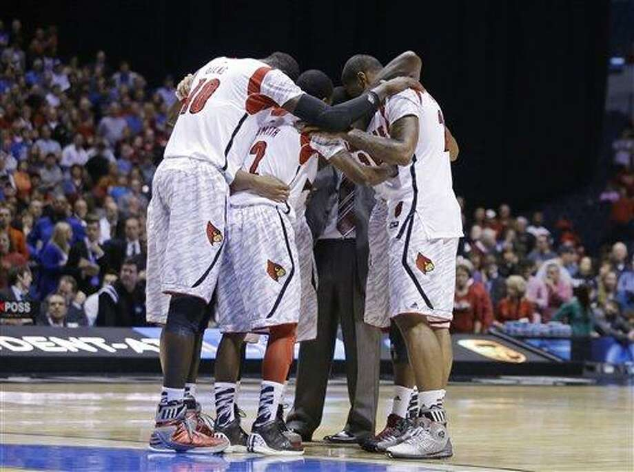 Louisville players huddle after guard Kevin Ware was taken out of the game after an injury during the first half of the Midwest Regional final against Duke in the NCAA college basketball tournament, Sunday, March 31, 2013, in Indianapolis. (AP Photo/Darron Cummings) Photo: AP / AP