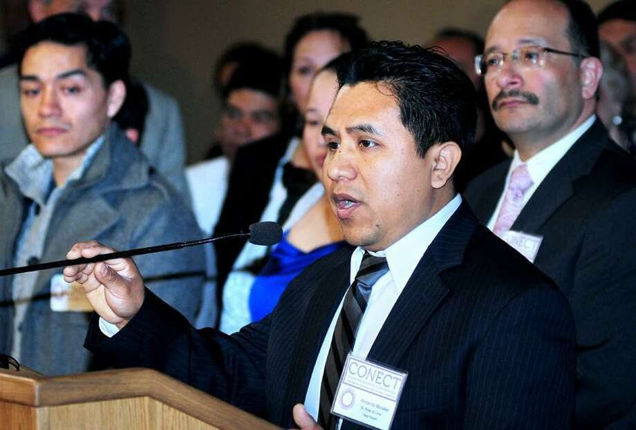 Armando Morales (center) of New Haven speaks at a press conference by CONECT, Congregations Organized for a New Connecticut, to push for legislation to enable undocumented immigrants to get drivers licenses at the Old Judicial Room at the Capitol in Hartford on 4/29/2013.Photo by Arnold Gold/New Haven Register    AG0494F