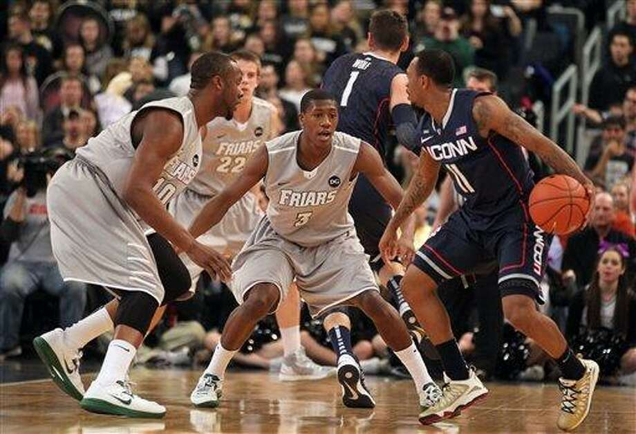 Providence guard Kris Dunn (3) and forward Kadeem Batts (10) defend against Connecticut guard Ryan Boatright (11) during the first half of an NCAA college basketball game, Thursday, Jan. 31, 2013, in Providence, R.I. (AP Photo/Stew Milne) Photo: AP / FR56276 AP