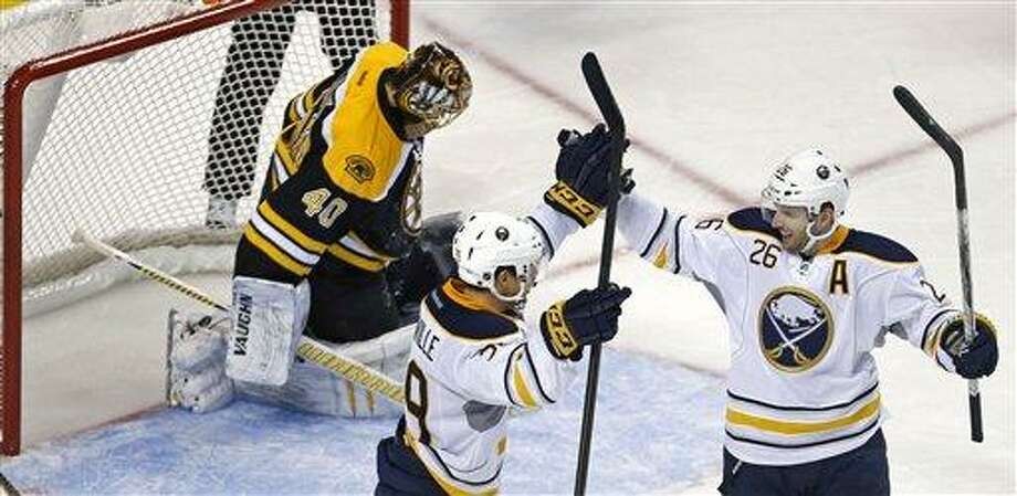 Buffalo Sabres left wing Thomas Vanek, right, of Austria, is congratulated by teammate Jason Pominville after beating Boston Bruins goalie Tuukka Rask, rear, during the third period of an NHL hockey game in Boston, Thursday, Jan. 31, 2013. Vanek scored three goals in the Sabres' 7-4 win. (AP Photo/Charles Krupa) Photo: AP / AP