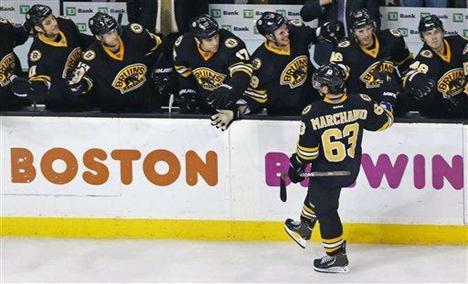 Boston Bruins left wing Brad Marchand (63) is congratulated by teammates after his goal against New Jersey Devils goalie Johan Hedberg in a shoot out following overtime of an NHL hockey game in Boston, Tuesday, Jan. 29, 2013. Marchand's goal put the Bruins ahead, giving them a 2-1 shoot out win. (AP Photo/Charles Krupa) Photo: AP / AP