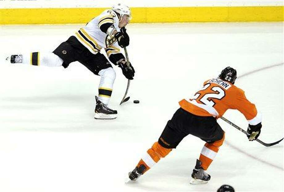 Boston Bruins' Brad Marchand (63) shoots on goal as Philadelphia Flyers' Luke Schenn (22) defends in the third period of an NHL hockey game, Saturday, March 30, 2013, in Philadelphia. The Flyers won 3-1. (AP Photo/Michael Perez) Photo: ASSOCIATED PRESS / AP2013