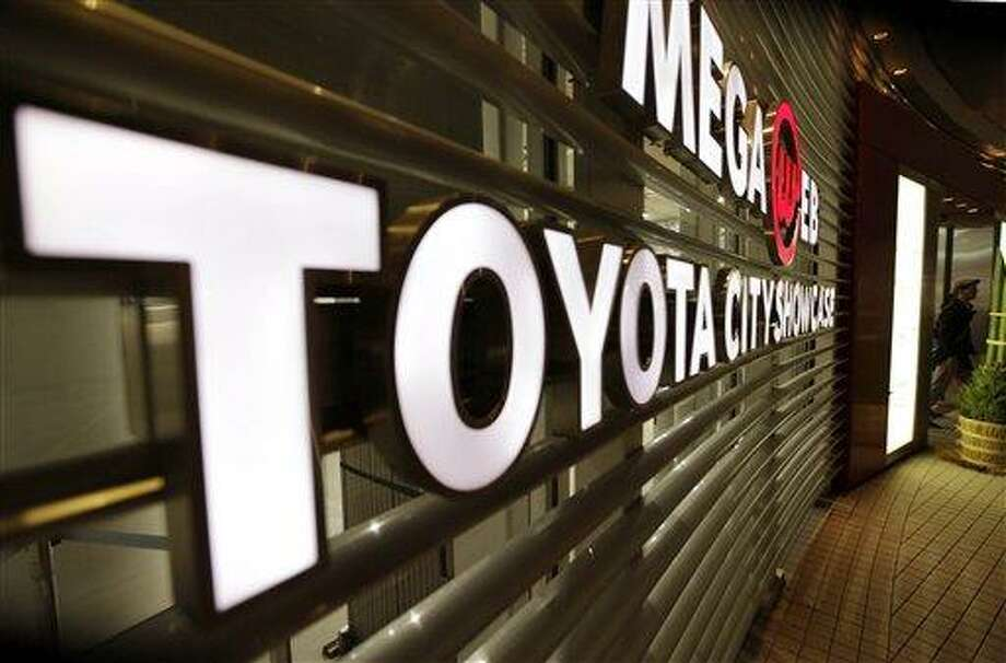 In this Dec. 27, 2012 photo, a man walks out from a Toyota showroom in Tokyo. Now it's official: Toyota is once again the world's top automaker. Toyota Motor Corp. released its tally for global vehicle sales for last year Monday, Jan. 28, 2013 at a record 9.748 million vehicles -- a bigger number than the estimate it gave last month of about 9.7 million vehicles. (AP Photo/Shizuo Kambayashi) Photo: AP / AP