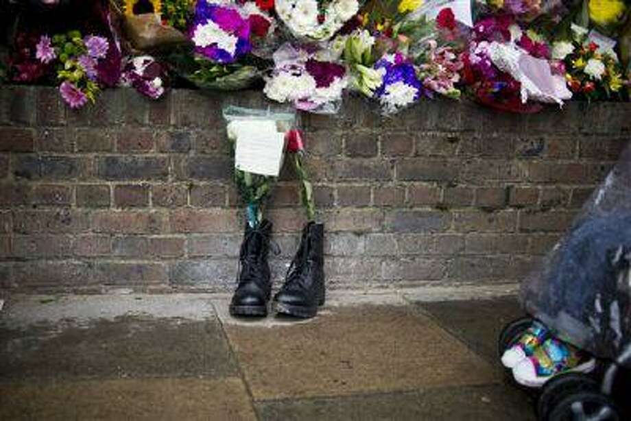 Military boots are laid in tribute outside the Woolwich Barracks, in London, in response to the bloody attack on May 22 when a British soldier was killed in the nearby street. Photo: AP / AP