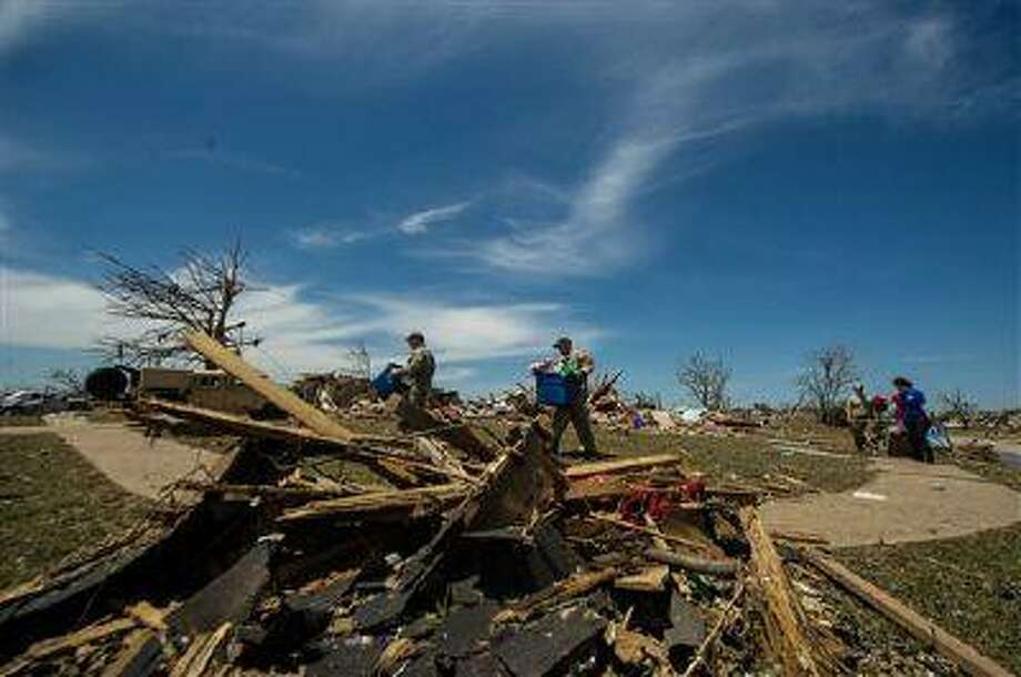 In this Wednesday, May 22, 2013 photo provided by the U.S. Air Force, U.S. Air Force Joint Terminal Attack Controller airmen help a resident in Moore, Okla., search through the debris looking for salvageable items. On Monday, a tornado leveled homes, crushed vehicles, and killed more than 20 people in the area. More than 115 Oklahoma National Guard personnel have been activated to assist in the rescue and relief efforts. (AP Photo/U.S. Air Force, Staff Sgt. Jonathan Snyder) Photo: ASSOCIATED PRESS / AP2013