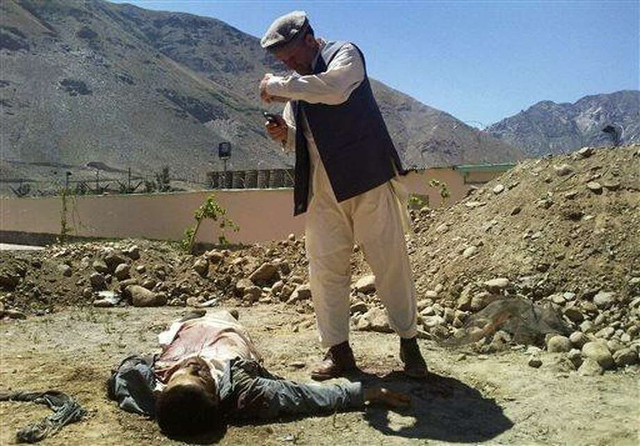 An Afghan man takes a photograph with his cell phone of an alleged insurgent who was shot and killed by government forces near a government compound in eastern Panjshir province, Afghanistan, Wednesday, May, 29, 2013. Afghan officials say one police officer was killed and another was wounded when seven insurgents attacked a government compound in eastern Panjshir province. (AP Photo) Photo: AP / AP