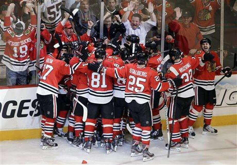 The Chicago Blackhawks celebrate after Brent Seabrook scored in overtime in Game 7 of the NHL hockey Stanley Cup Western Conference semifinals against the Detroit Red Wings, Wednesday, May 29, 2013, in Chicago. The Blackhawks won 2-1. (AP Photo/Nam Y. Huh) Photo: AP / AP