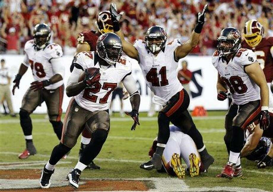 Tampa Bay Buccaneers running back LeGarrette Blount (27) scores against the Washington Redskins during the fourth quarter of an NFL football game, Sunday, Sept. 30, 2012, in Tampa, Fla. Fullback Erik Lorig (41) and tight end Luke Stocker (88) celebrate the touchdown. The Redskins won 24-22. (AP Photo/Chris O'Meara) Photo: ASSOCIATED PRESS / AP2012