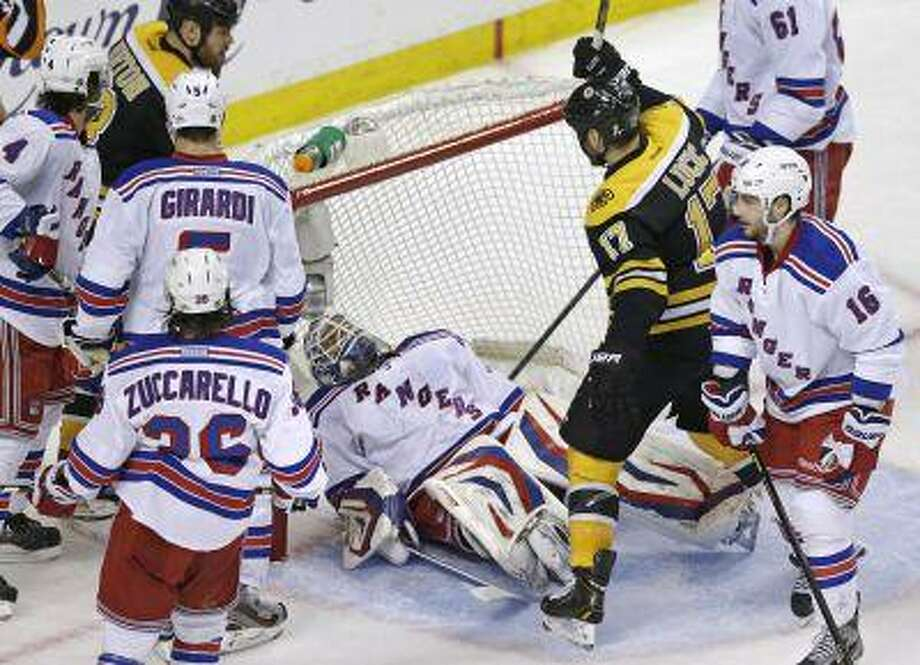 Boston Bruins left wing Milan Lucic (17) raises his stick to celebrate a goal by teammate Zdeno Chara (not shown) as New York Rangers goalie Henrik Lundqvist, center, falls onto his back during the second period in Game 1 of an NHL hockey playoffs Eastern Conference semifinal game in Boston, Thursday, May 16, 2013. Photo: ASSOCIATED PRESS / AP2013