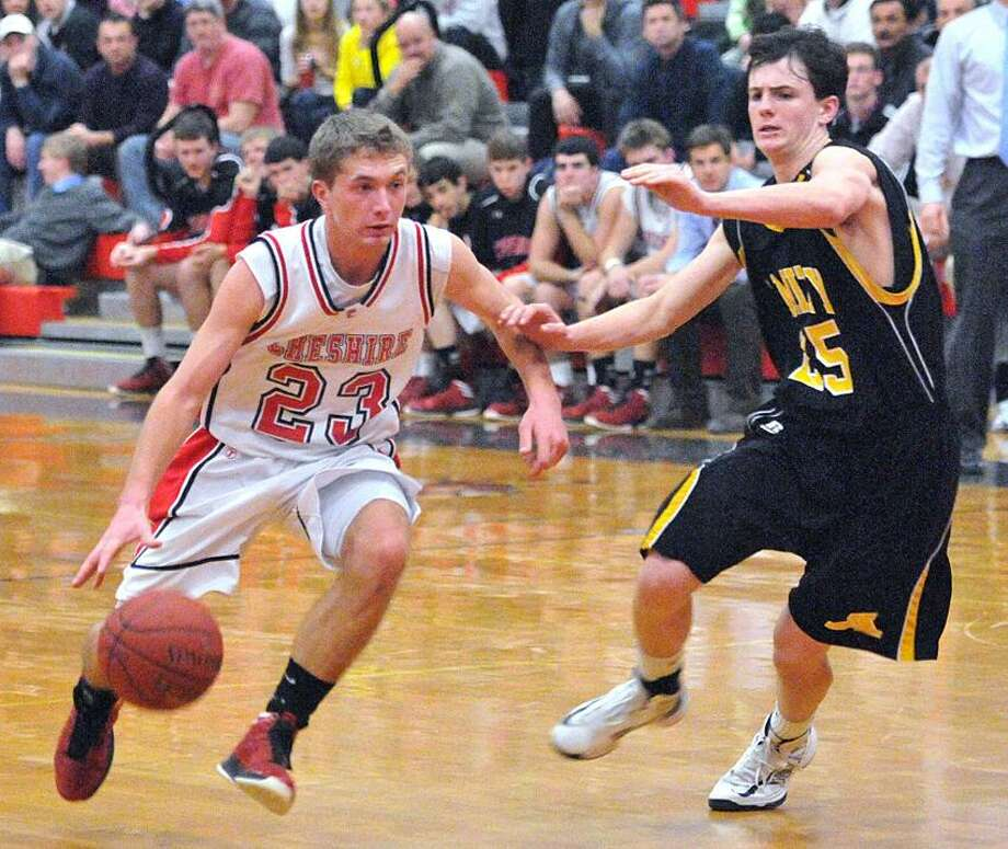 Cheshire-- Cheshire's Eric Dietrich drives past Amity's Dave Ryan during the first half. Photo-Peter Casolino 1/25/13