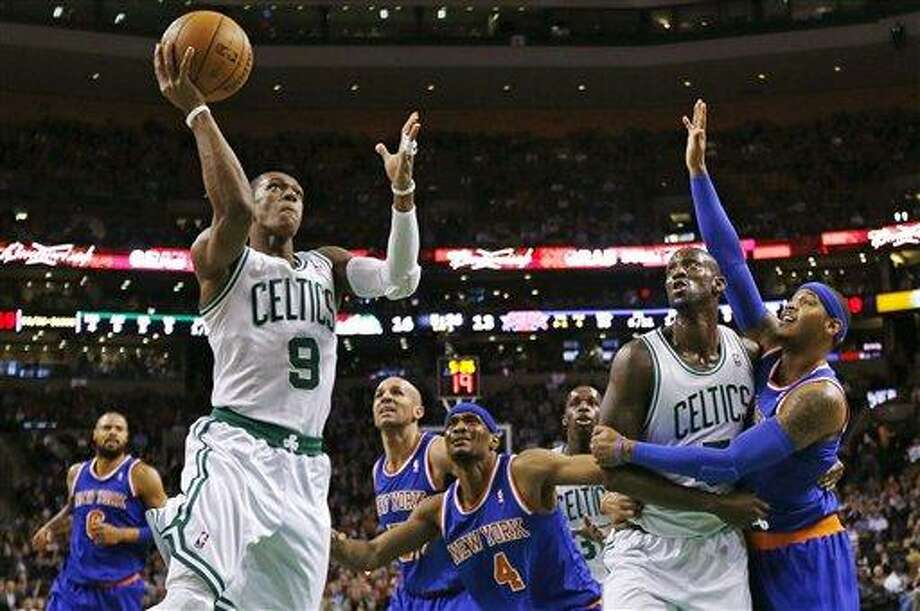 Boston Celtics guard Rajon Rondo (9) drives to the basket as Kevin Garnett blocks out New York Knicks forward Carmelo Anthony, right, during the first quarter of an NBA basketball game in Boston, Thursday, Jan. 24, 2013. (AP Photo/Charles Krupa) Photo: AP / AP