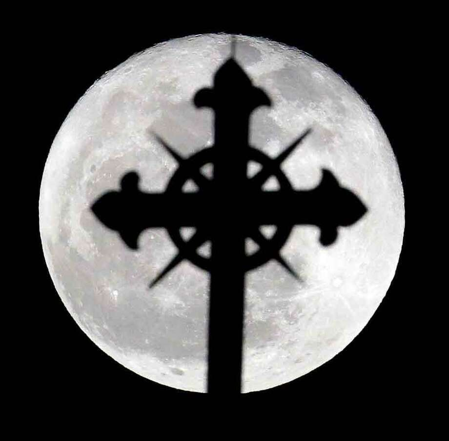 A full moon rises behind a cross on top of Saint Nicholas Catholic Church in the Heights neighborhood of Jersey City, N.J., Wednesday, March 27, 2013. Catholics are observing Holy Week, which is the final week of the Lent period before Easter. (AP Photo/Julio Cortez) Photo: ASSOCIATED PRESS / AP2013