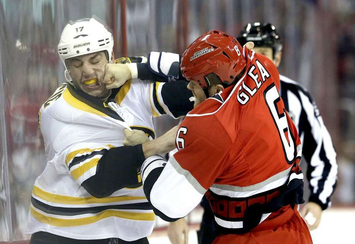 Carolina Hurricanes' Tim Gleason (6) hits Boston Bruins' Milan Lucic (17) while fighting during the first period of an NHL hockey game in Raleigh, N.C., Monday, Jan. 28, 2013. (AP Photo/Gerry Broome)