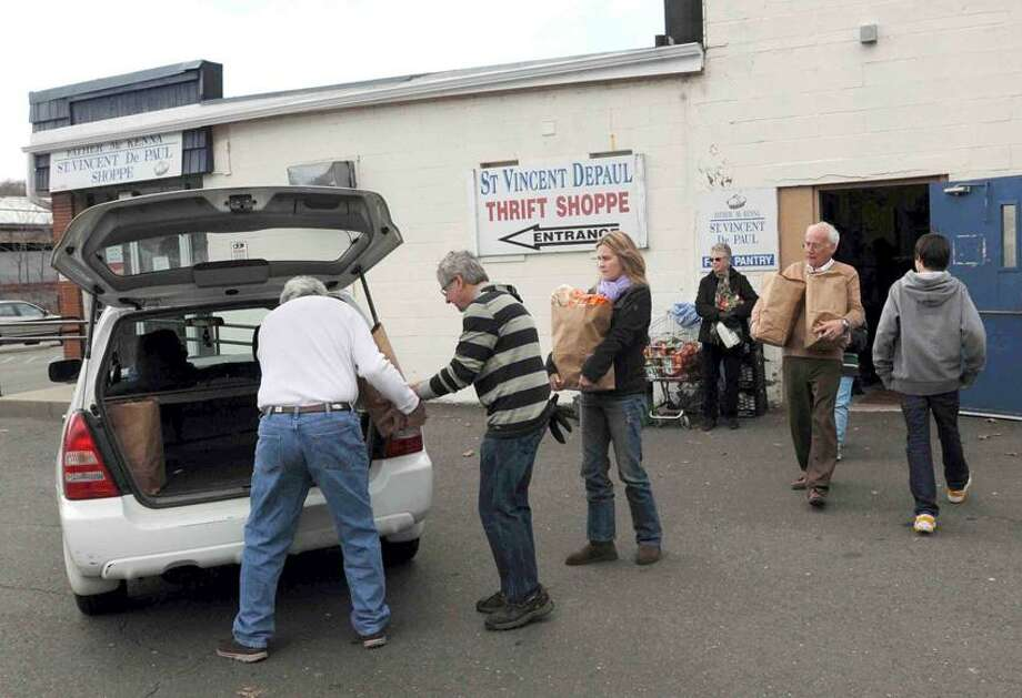 St. Vincent De Paul Helping Hands of the Valley Thrift Shop and Food Pantry volunteers in Derby Wednesday March 27, 2013 bring food out to waiting cars during their annual distribution of Easter gifts and food for holiday dinner to more than 100 needy families. Photo by Peter Hvizdak / New Haven Register Photo: New Haven Register / ©Peter Hvizdak /  New Haven Register