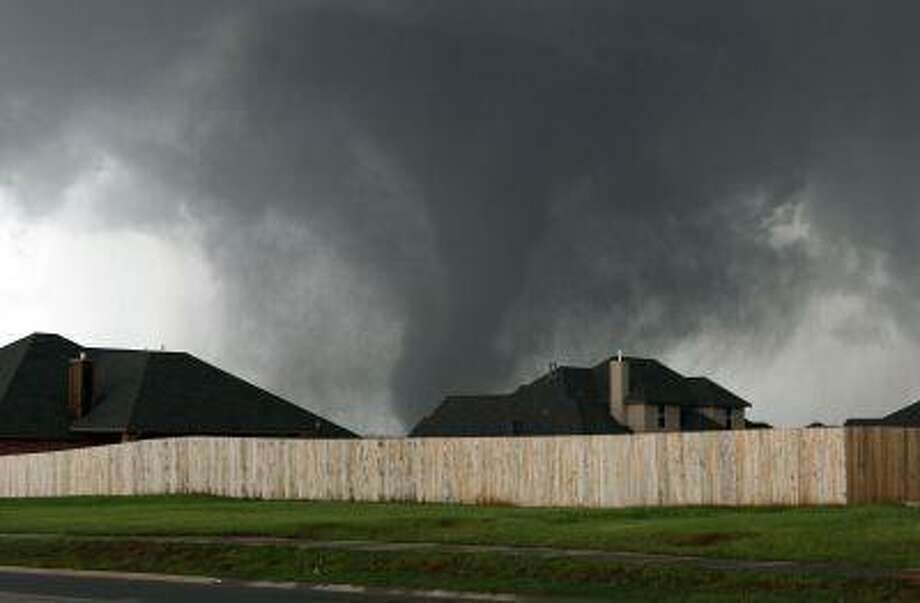 A tornado moves past homes in Moore, Okla. on May 20. (Alonzo Adams/AP) Photo: AP / FR159426 AP