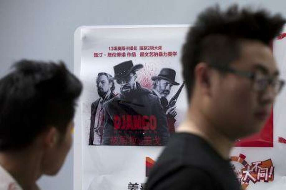 """People walk past a poster of Quentin Tarantino's movie""""Django Unchained"""" in Beijing Monday, May 13, 2013. Photo: ASSOCIATED PRESS / AP2013"""