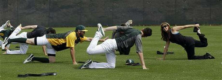 Oakland Athletics pitchers Ryan Cook, left, and Jerry Blevins, center, perform yoga stretches with the help of instructor Katherine Roberts before an exhibition spring training baseball game against the Colorado Rockies on Wednesday, March 27, 2013 in Phoenix. (AP Photo/Marcio Jose Sanchez) Photo: AP / AP
