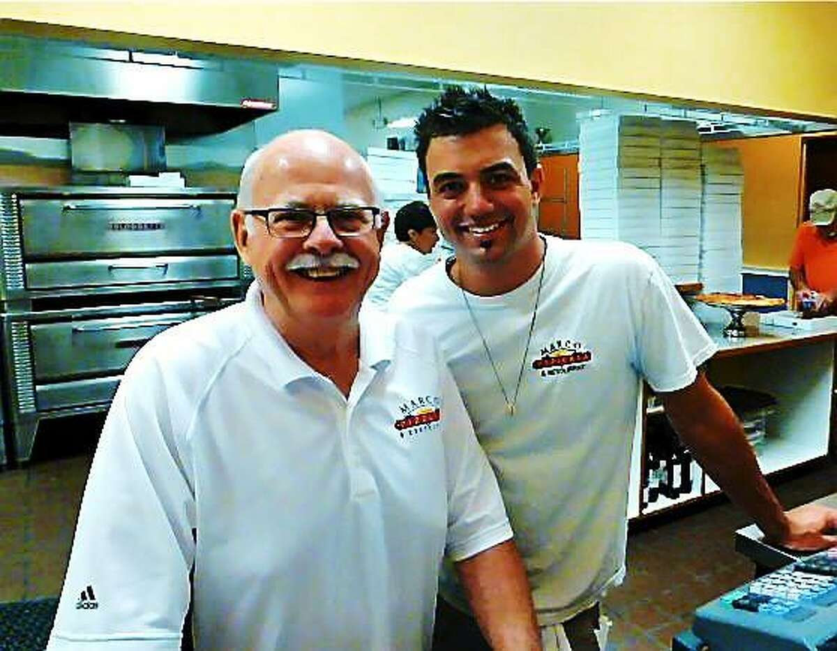 Tom Andrew, owner of Marco Pizzeria and Restaurant in Derby, left, and restaurant manager Jordan Mann take a break in the kitchen during Monday's fund-raising event. Patricia Villers/Register