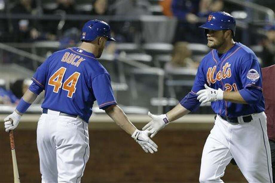 New York Mets' John Buck (44) greets teammate Lucas Duda (21) after Duda hit a fourth-inning solo home run off Atlanta Braves starting pitcher Julio Teheran in a baseball game at Citi Field in New York, Sunday, May 26, 2013. (AP Photo/Kathy Willens) Photo: AP / AP