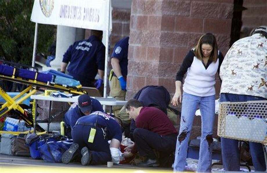 FILE - Emergency personnel attend to a shooting victim  outside a shopping center in Tucson, Ariz. in this Saturday, Jan. 8, 2011 file photo taken where U.S. Rep. Gabrielle Giffords, D-Ariz., and others were shot as the congresswoman was meeting with constituents. Hundreds of pages of police reports in the investigation of the Tucson shooting rampage that wounded former Rep. Gabrielle Giffords are being released Wednesday, March 27, 2013 marking the public's first glimpse into documents that authorities have kept private since the attack more than two years ago.  (AP Photo/James Palka, File) Photo: AP / PALKJ