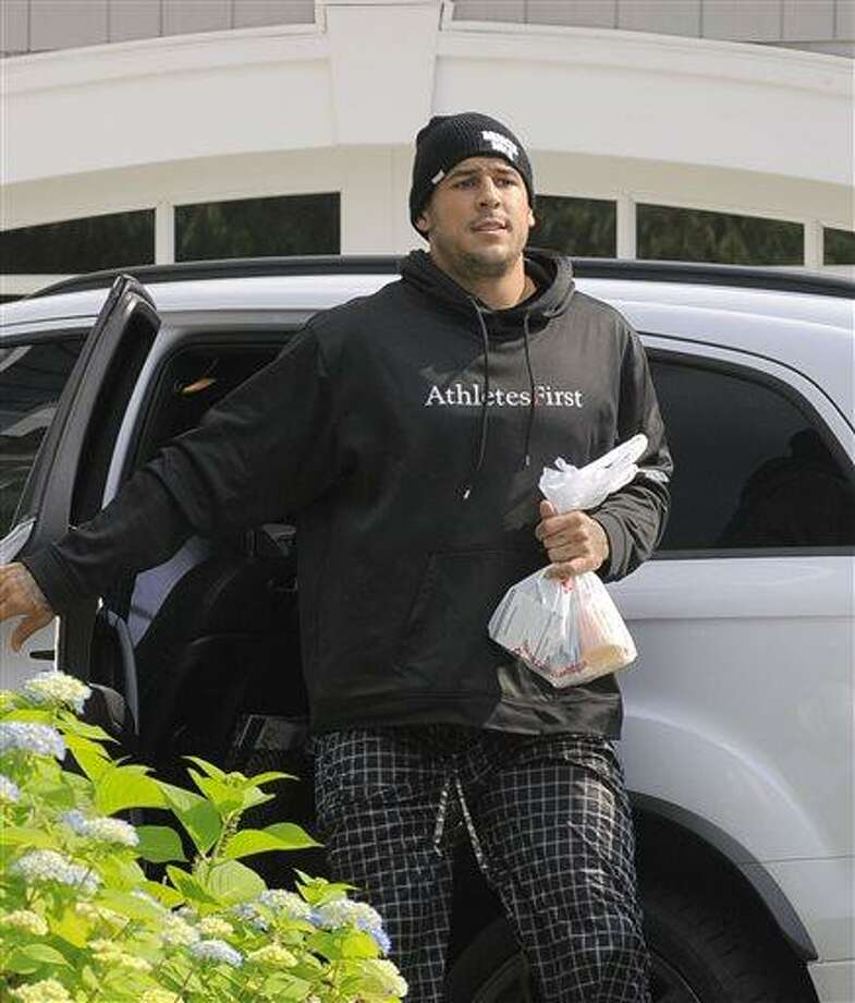 Aaron Hernandez returns to his home at Friday, June 21, 2013 in North Attleboro, Mass. At least one company yanked an endorsement deal from New England Patriots tight end Aaron Hernandez on Friday as puzzled family members of a friend found slain a mile from Hernandez's home sought answers about how he died. (AP Photo/The Boston Herald, Ted Fitzgerald)  BOSTON GLOBE OUT; METRO BOSTON OUT; MAGS OUT; ONLINE OUT; MANDATORY CREDIT Photo: AP / The Boston Herald