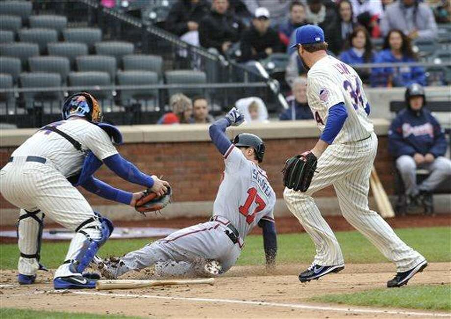 Atlanta Braves' Jordan Schafer (17) scores at home plate under the tag of New York Mets catcher John Buck, left, as relief pitcher Brandon Lyon (34) watches in the tenth inning of a baseball game that was suspended from Friday night at Citi Field, Saturday, May 25, 2013, in New York. The Braves won 7-5. (AP Photo/Kathy Kmonicek) Photo: AP / FR170189 AP