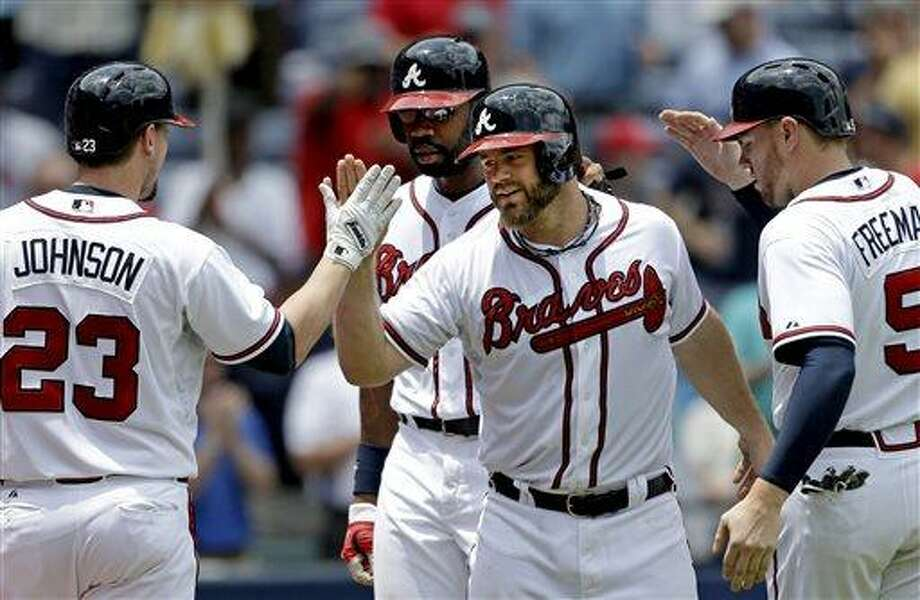 In this photo taken Wednesday, May 22, 2013, Atlanta Braves' Evan Gattis, second from right, is greeted by teammates from left, Chris Johnson, Jason Heyward, and Freddie Freeman after hitting a grand slam in the fourth inning of a baseball game against the Minnesota Twins in Atlanta.  It's hard not to get caught up in this modern-day tale, a guy who quit baseball for nearly four years, yet found his way back. Gattis made the Braves as a non-roster player, and has become a downright sensation as a 26-year-old rookie. (AP Photo/David Goldman) Photo: AP / AP
