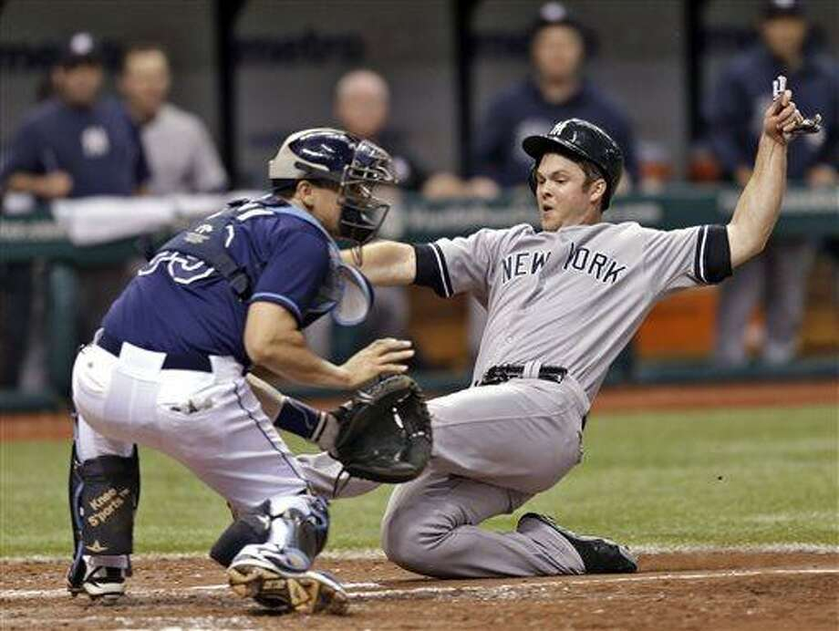 New York Yankees' Brennan Boesch scores ahead of the tag by Tampa Bay Rays catcher Jose Lobaton during the ninth inning of a baseball game, Saturday, May 25, 2013, in St. Petersburg, Fla. Boesch scored on an RBI single by Brett Gardner. (AP Photo/Chris O'Meara) Photo: AP / AP