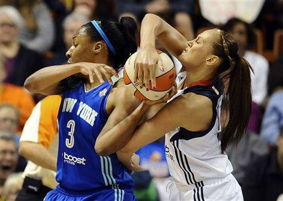 Connecticut Sun's Mistie Bass, right, strips the ball from New York Liberty's Kelsey Bone, left, during the first half of a WNBA basketball game in Uncasville, Conn., Saturday, May 25, 2013. (AP Photo/Jessica Hill) Photo: AP / FR125654 AP