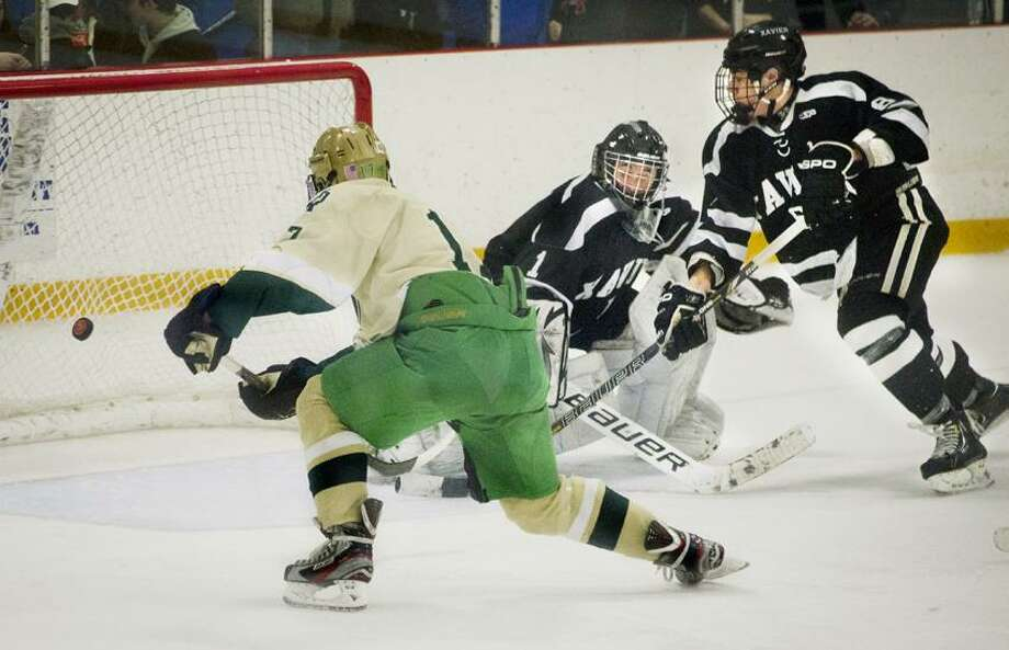 SPORTS--Notre Dame  vs. Xavier Hockey -- Jesse Ruocco scores in 3rd period action. Trying to assist goalie, Ben Guidobono, is teammate, Cam Pollack.  Photos by  Melanie Stengel