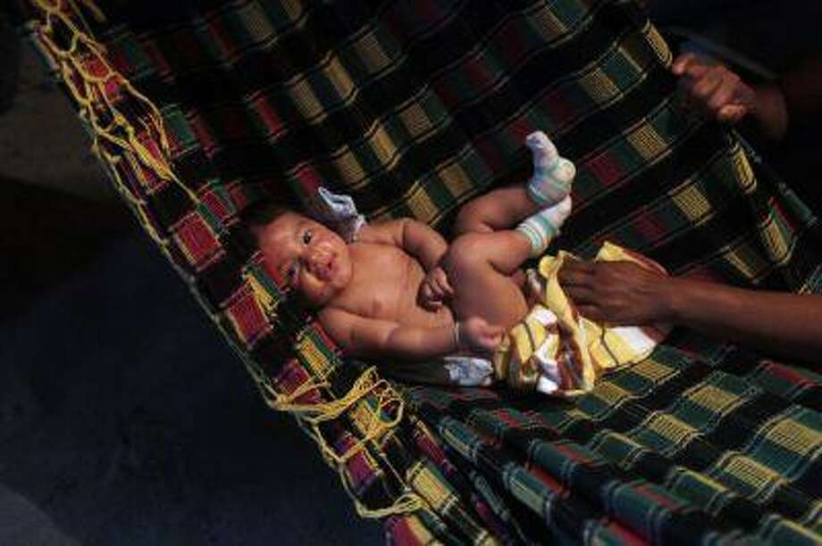 A baby rests on a hammock. REUTERS/Pilar Olivares Photo: REUTERS / X00856