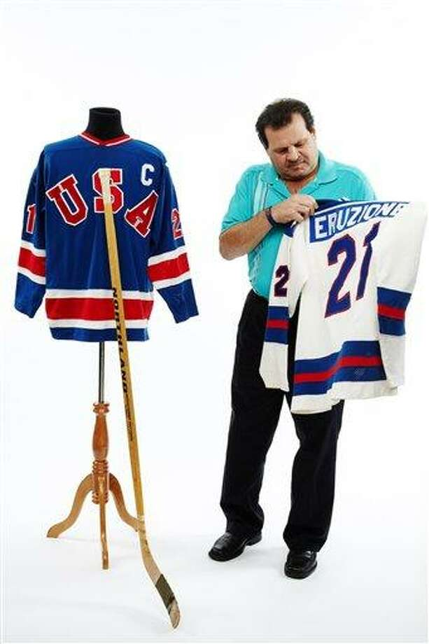 This Dec. 12, 2012 handout photo, provided by Heritage Auctions, shows former United States Olympic hockey player Michael Eruzione in Dallas with jerseys and the hockey stick from his sensational winning goal against the Soviet Union hockey team at the 1980 Winter Olympics. The 'Miracle On Ice' paraphernalia will be offered by Dallas-based Heritage Auctions in New York on Feb. 22, on the 33rd anniversary of that historic game. (AP Photo/Courtesy of Heritage Auctions) Photo: AP / Heritage Auctions