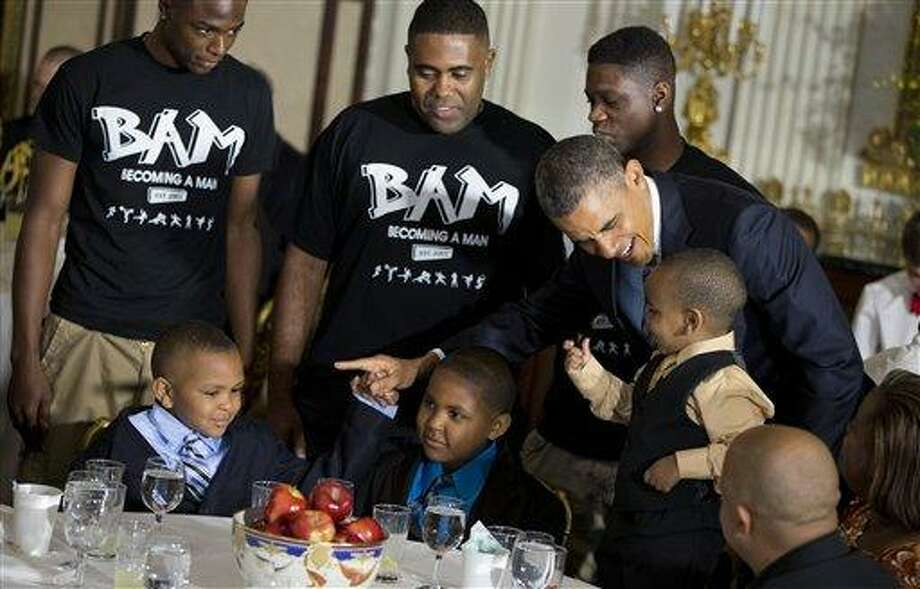 President Barack Obama greets guests, including fathers and their children participants in the Becoming a Man (BAM) program at Hyde Park Academy in Chicago, Friday, June 14, 2013, in the State Dining Room of the White House in Washington, where the president hosted a Father's Day luncheon.  (AP Photo/Evan Vucci) Photo: AP / AP